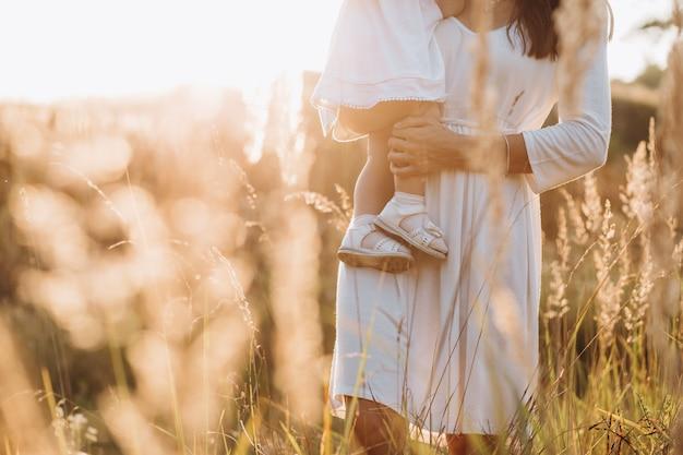 Bello ritratto della madre affascinante e della piccola figlia adorabile che camminano attraverso il campo