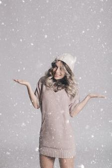 Bello ritratto di giovane donna attraente in vestiti tricottati su fondo nevoso