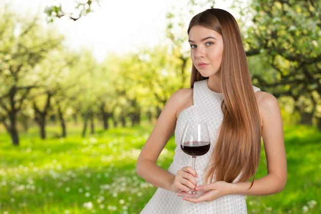 Bello ritratto di modello isolato sopra la priorità bassa dello studio che tiene il vetro di vino