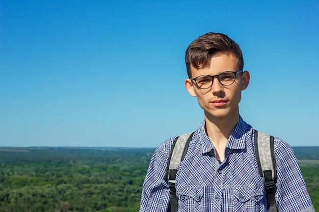 Bello ritratto di un giovane con i vetri su una priorità bassa del cielo blu.