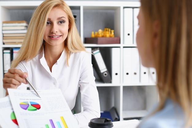 Bello ritratto sorridente della donna di affari nel luogo di lavoro