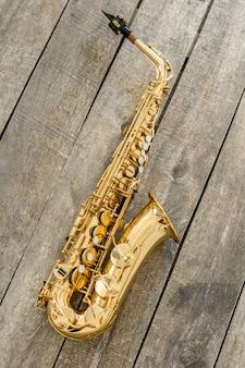 Bello sassofono dorato su fondo di legno
