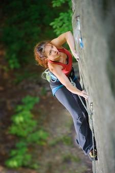 Bello scalatore della donna che scala roccia ripida con la corda