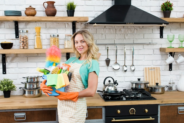 Bello secchio della tenuta della donna degli strumenti e dei prodotti di pulizia che stanno nella cucina
