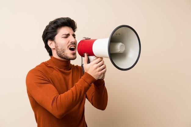 Bello sopra isolato muro urlando attraverso un megafono