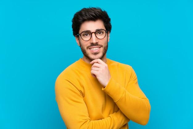 Bello sopra la parete blu isolato con occhiali e sorridente