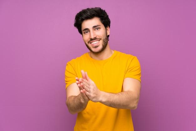 Bello sopra la parete viola isolata che applaude dopo la presentazione in una conferenza