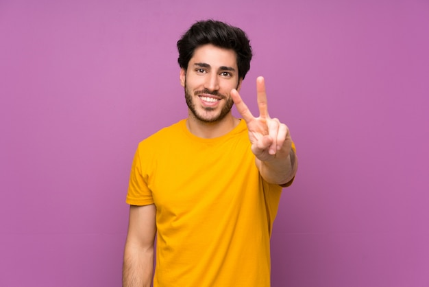 Bello sopra la parete viola isolata che sorride e che mostra il segno di vittoria