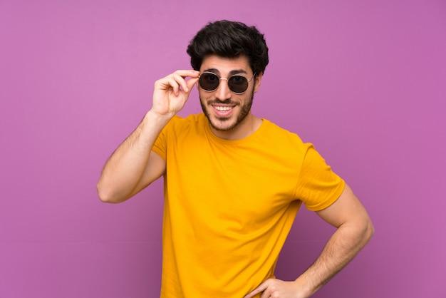 Bello sopra la parete viola isolata con gli occhiali e sorpreso