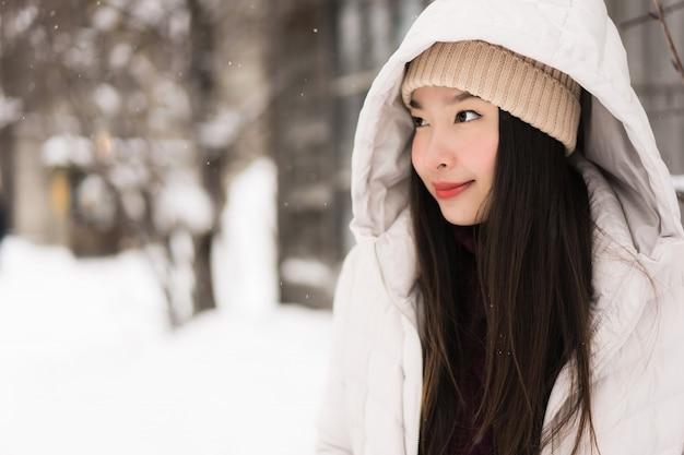 Bello sorridere asiatico della giovane donna felice per il viaggio nella stagione invernale della neve