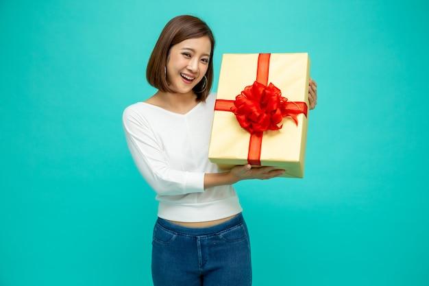 Bello sorriso asiatico felice della donna con il contenitore di regalo dell'oro isolato sulla parete verde. ragazze innamorate, ricevono regali dagli innamorati. concetto di natale o capodanno