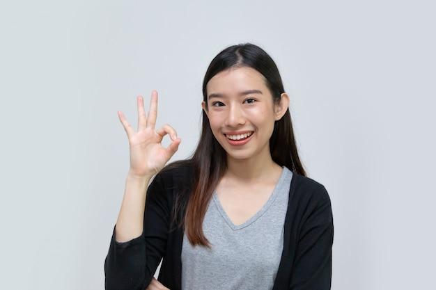Bello sorriso della giovane donna asiatica felice con il gesto giusto isolato