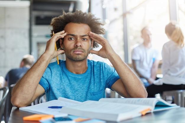 Bello studente barbuto dalla pelle scura con taglio di capelli afro che stringe le tempie, avendo mal di testa mentre si prepara per esami o test notte e giorno, guardando con espressione dolorosa e frustrata