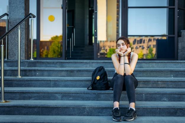 Bello studente premuroso che si siede sulle scale all'aperto tra le classi. la vita studentesca, il concetto di educazione