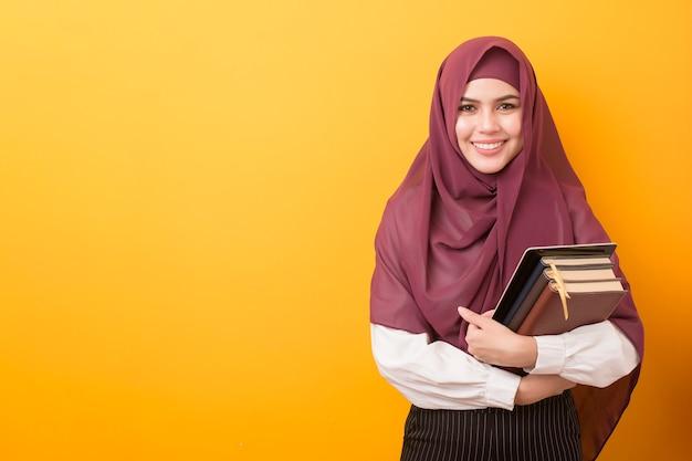 Bello studente universitario con il ritratto di hijab su fondo giallo