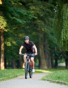 Bello tonico ciclista ragazzo in abiti da ciclismo, guardando alla telecamera, mentre in sella a bici lungo il vicolo del parco in giornata estiva