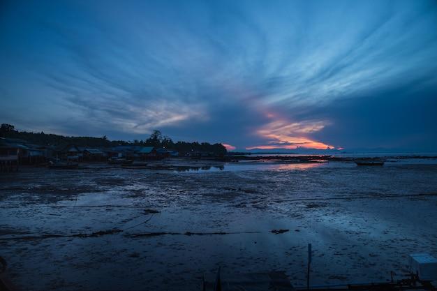 Bello tramonto durante la bassa marea sulla spiaggia del villaggio di koh libong, trang, tailandia