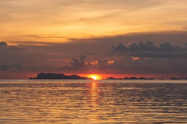 Bello tramonto tropicale della spiaggia con il fondo delle luci dorate