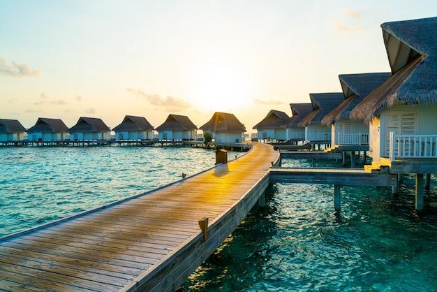 Bello tramonto tropicale sopra l'isola delle maldive con il bungalow dell'acqua nella località di soggiorno dell'hotel