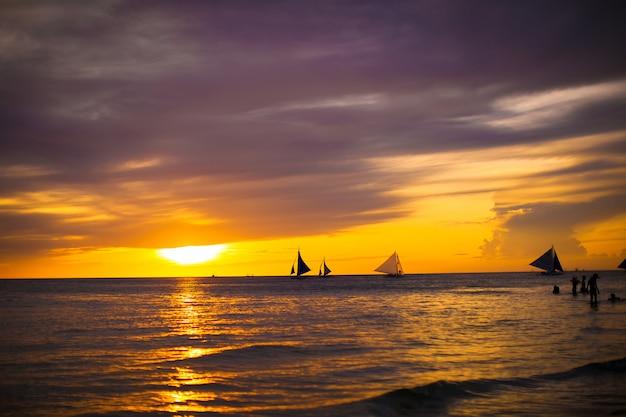 Bello tramonto variopinto con la barca a vela sull'orizzonte nell'isola di boracay