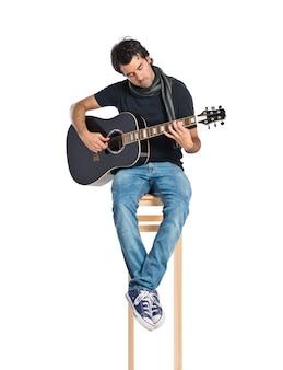 Bello uomo con chitarra su sfondo bianco