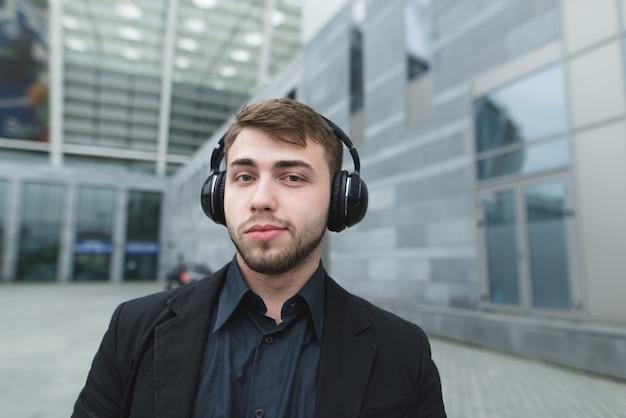 Bello uomo con la barba e un vestito che ascolta la musica in cuffia contro il paesaggio urbano.