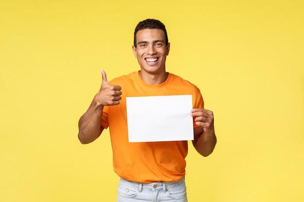 Bello uomo felice felice soddisfatto in maglietta arancio che tiene una carta