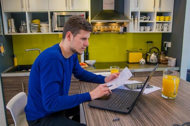 Bello uomo moderno progettista lavorando a casa utilizzando laptop a casa. felice uomo che lavora da casa con tablet digitale e computer portatile