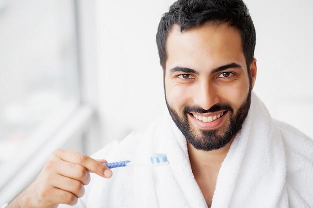 Bello uomo sorridente che pulisce i denti bianchi sani con la spazzola.
