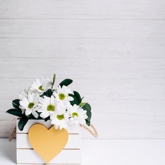 Bello vaso di fiore bianco decorativo con forma del cuore contro il contesto di legno