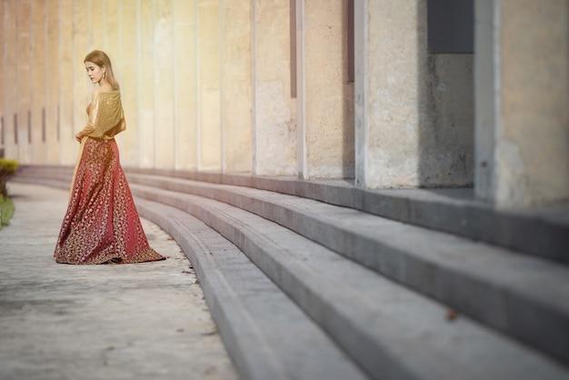 Bello vestito asiatico dalla donna in vestito da sera di seta tailandese