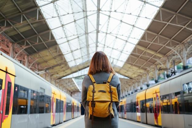 Bello viaggiatore portoghese della donna che aspetta alla stazione ferroviaria. concetto di viaggio e vacanza. stile di vita urbano.