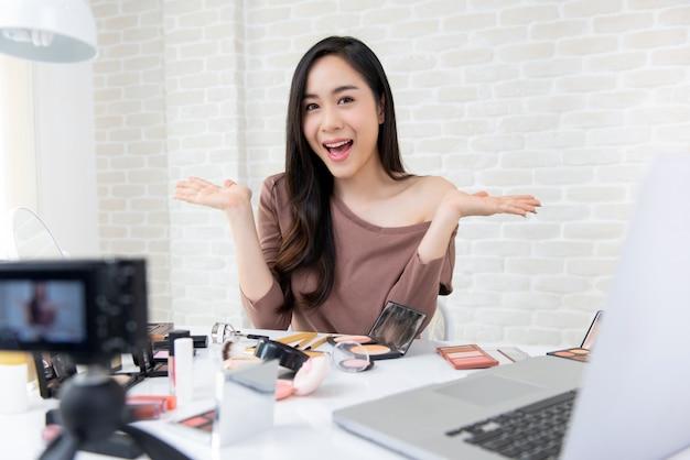 Bello vlogger asiatico di bellezza della donna che registra tutorial cosmetico di trucco