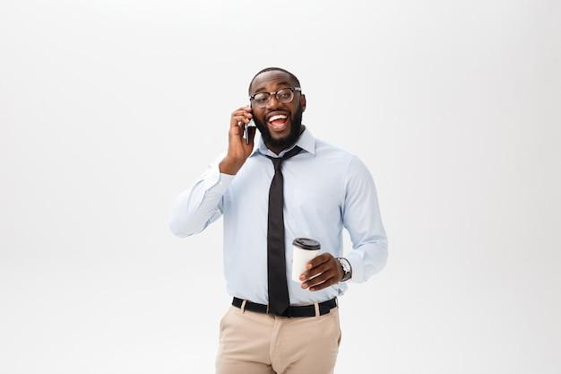 Ben detto. giovane uomo africano allegro in camicia bianca che tiene una tazza di caffè e che parla sul telefono cellulare