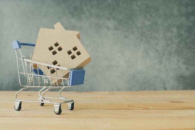 Bene immobile ed acquisto e vendita del concetto domestico, modello della casa in carrello sulla tavola di legno