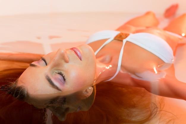 Benessere, giovane donna che galleggia nella spa o in piscina