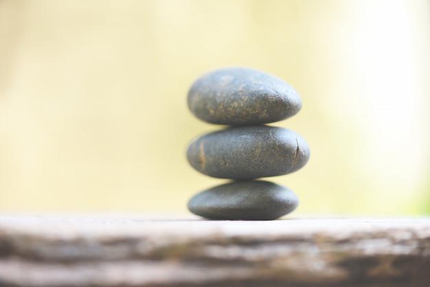 Benessere naturale rilassati con le pietre zen sulla natura verde spa. terapia alternativa naturale con pietre da massaggio