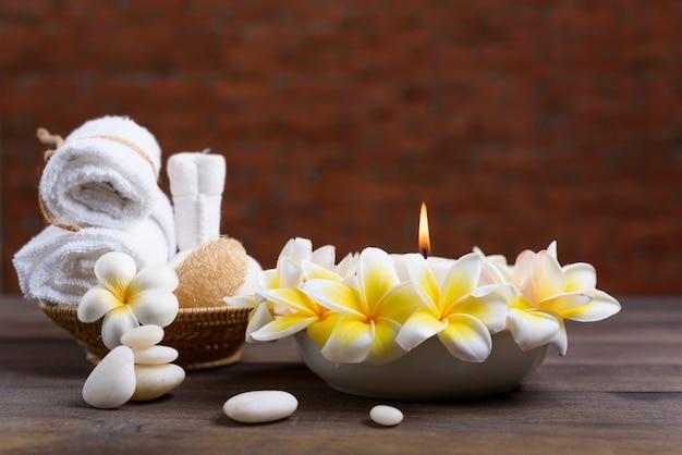 Benessere termale e trattamento con olii essenziali, pietra zen, asciugamani, candele, pallina per massaggi acustici e fiori di frangipane sul tavolo di legno con muro di mattoni