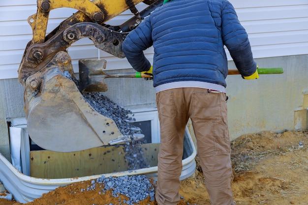 Benna che sposta la ghiaia nelle finestre bene sulla costruzione del seminterrato dalla finestra