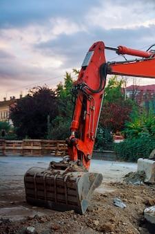 Benna dell'escavatore che scava la terra per l'installazione dei tubi la via