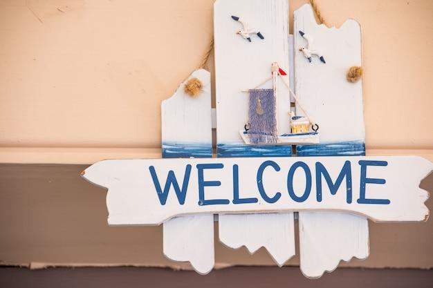 Benvenuto segno appeso su fondo in legno rustico.