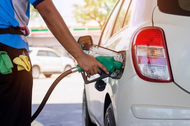 Benzina di rifornimento dell'automobile bianca dall'ugello dell'erogatore automatico alla stazione di servizio con luce solare calda