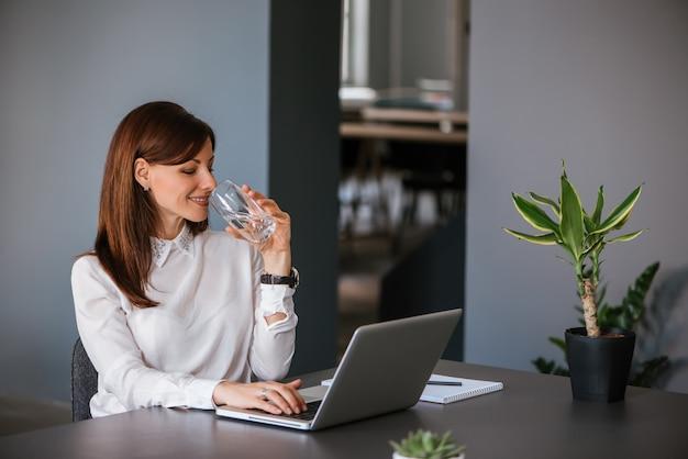 Bere acqua mentre si lavora con il computer portatile