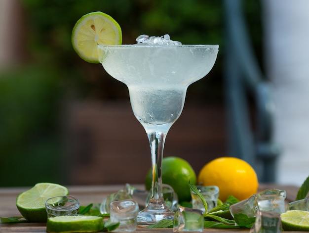 Bere cocktail fresco con alcool, cubetti di ghiaccio e una fetta di lime in un bicchiere