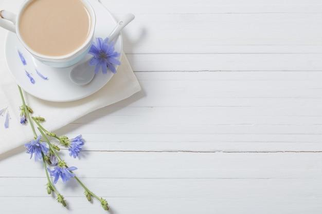 Bere dalla cicoria in una tazza sul tavolo di legno bianco