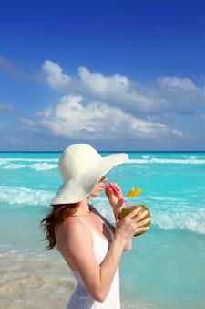 Bere fresco della donna della spiaggia di profilo del cocktail della noce di cocco
