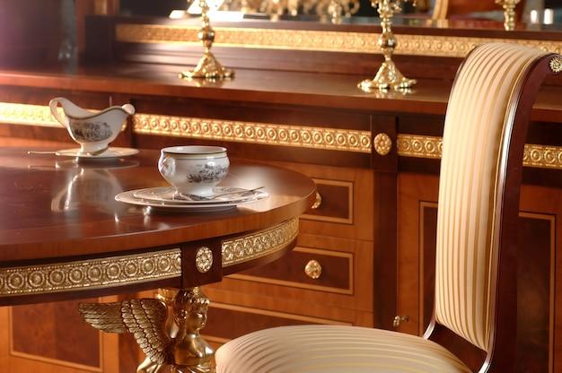 Bere il tè al tavolo sulla poltrona e mobili in legno