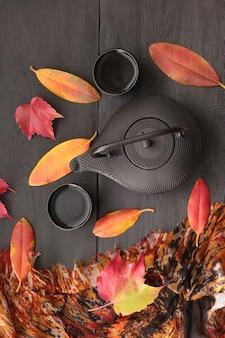 Bere il tè in autunno. umore del tè d'autunno. teiera nera e foglie di autunno