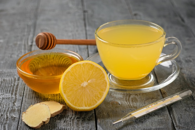 Bere radice di zenzero, limone, arancia, miele e cannella e termometro su un tavolo di legno nero.