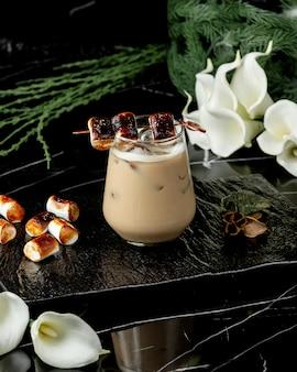 Bere un bicchiere di caffè con ghiaccio guarnito con marshmallow tostato